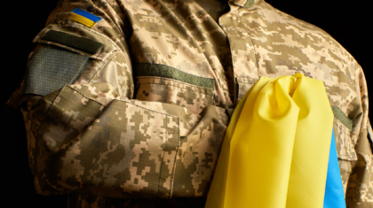 Ukrainian soldier holds in his hand the yellow-blue flag of the